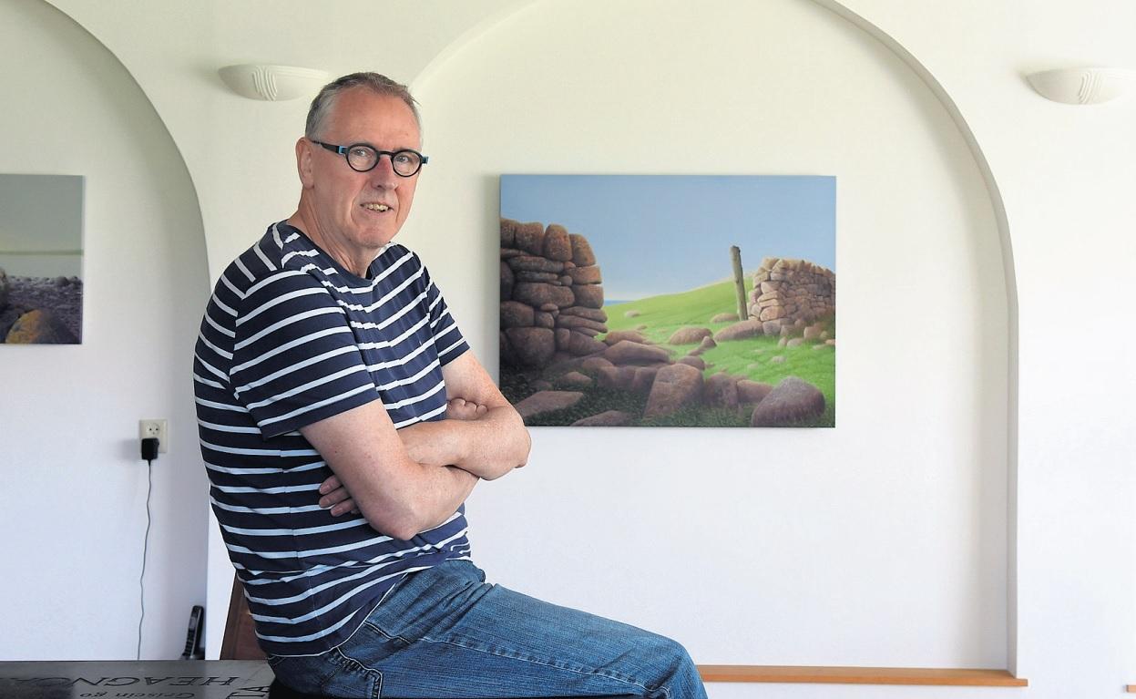 Reinder Ourensma in zijn woonkamer met achter hem zijn recente werk Separated for too long VIII (acryl, 2017). In het gedetailleerd schilderen van onder meer gras en stenen, daagt de Leeuwarder kunstenaar zichzelf uit om tot het uiterste te gaan. Foto: Marchje Andringa
